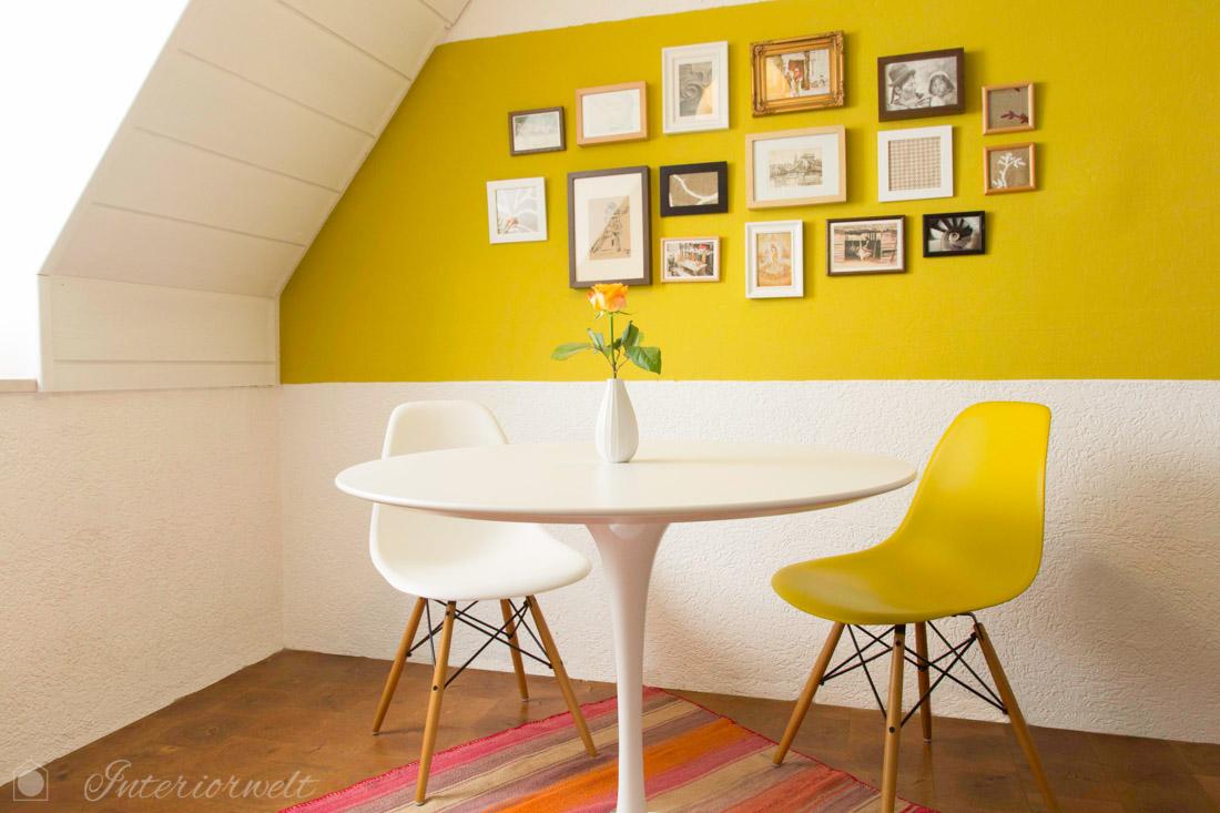 Esstisch und gelb-grüne Wand mit Bildern