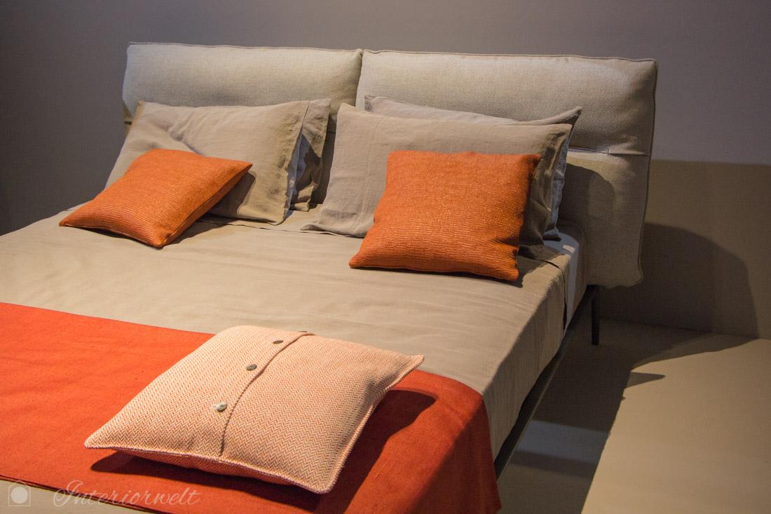 Orange Kissen auf Bett